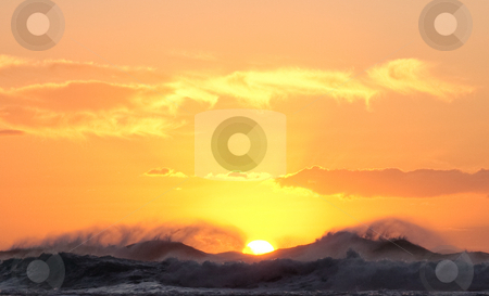Sun setting over stormy sea stock photo, Sun sinking below horizon over windswept waves by Steven Heap