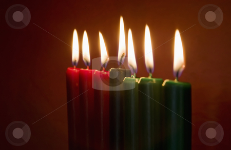 Kwanzaa Candles stock photo, Seven Kwanzaa candles with flames lit on neutral background by Scott Griessel
