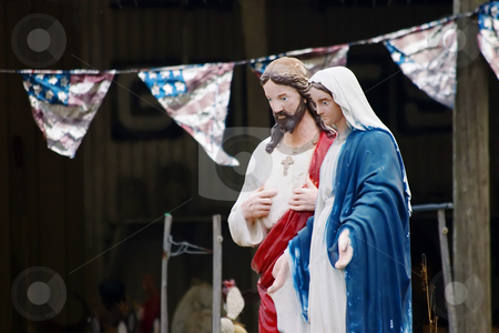 Kitsch statues of Jesus and Mary stock photo, Kitsch statues of jesus and Mary in front of an American Flag banner by Scott Griessel