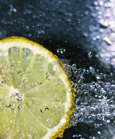 Refreshing lemon stock photo, Water splashing onto a lemon - focus is on the water drops by Kirsty Pargeter