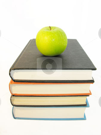 Apple on stacked books stock photo,  by Kirsty Pargeter