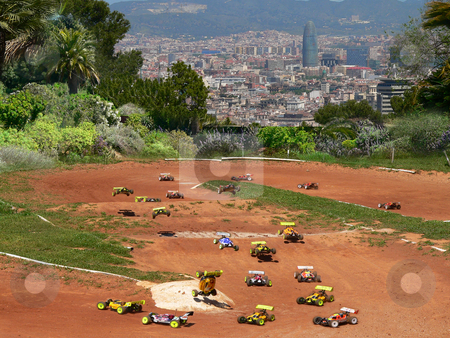 Minature motor racing stock photo, Model cars racing around a dirt track with a view of palm trees and the agbar tower of barcelona in spain by Casinozack