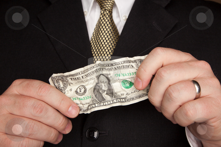 Businessman Holding Wrinkled Dollar Bill stock photo, Businessman with Coat and Tie Holding Wrinkled United States Dollar Bill. by Andy Dean