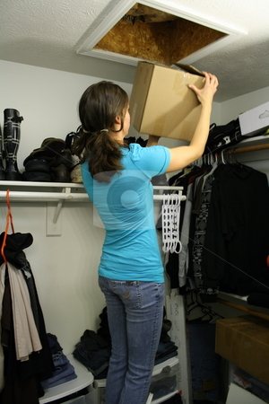 Girl taking boxes down from attic stock photo, Girl takes down boxes from attic by Chris Torres