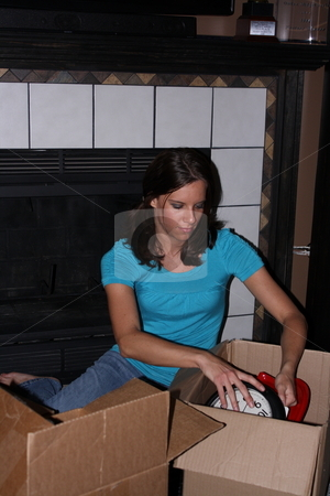 Girl sorting through boxes stock photo, A girl searching through boxes trying to find items to list in online auctions. by Chris Torres