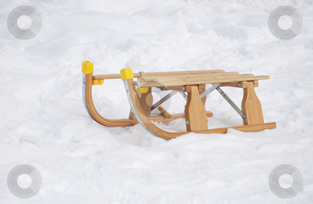 Sledge in snow stock photo, Old fashioned wooden sledge in the snow. by Ivan Paunovic