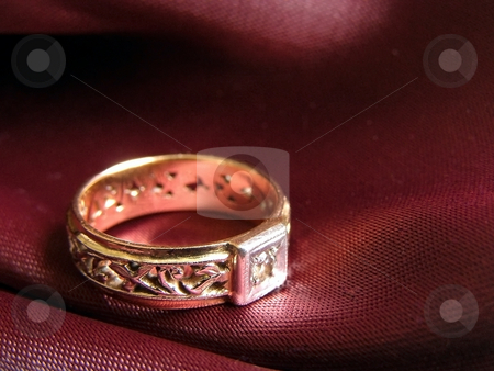 Golden ring stock photo, Golden ring on the red against dark background by Sergej Razvodovskij