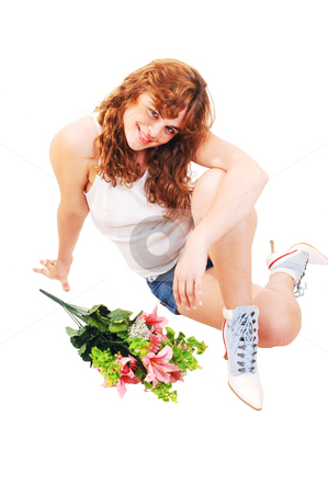 Girl sitting on floor. stock photo, A young red haired girl in t-shirt and short shorts sitting on the floor, smiling with a bunch of flowers in front of her. by Horst Petzold