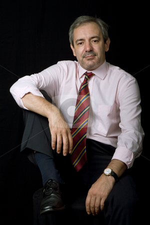 Seated stock photo, Mature business man portrait on black background by Rui Vale de Sousa