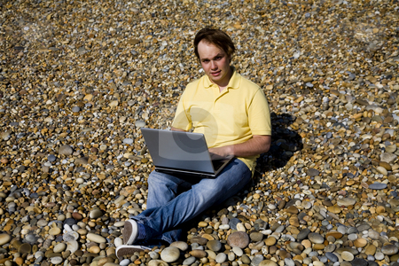 Working stock photo, Young man at the beach working with laptop by Rui Vale de Sousa