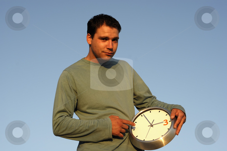 Clock stock photo, Young man with a clock at sunset light by Rui Vale de Sousa