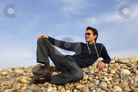 Sunbath stock photo, Young casual man at the beach stones by Rui Vale de Sousa
