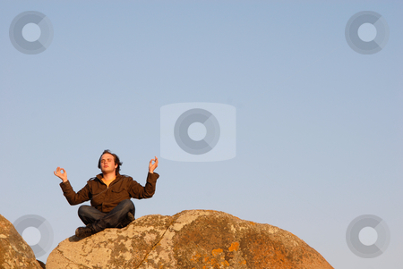 Yoga stock photo, Young man meditating on the rocks with the sky as background by Rui Vale de Sousa