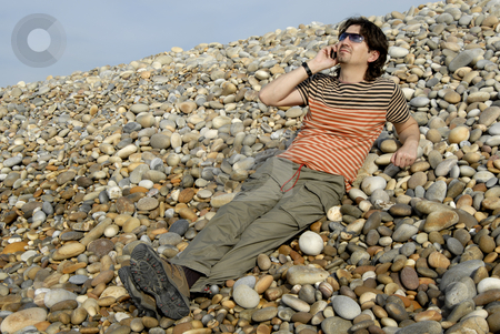 Calling stock photo, Young man on the beach with cell phone by Rui Vale de Sousa