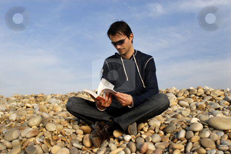 Read stock photo, Young man with a book at the beach by Rui Vale de Sousa