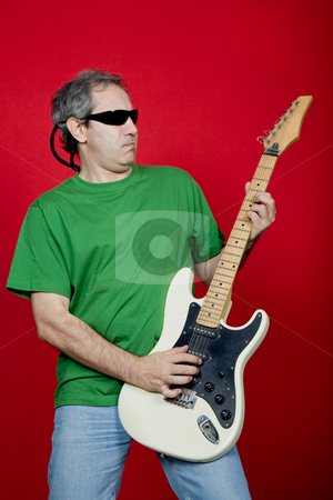 Play stock photo, Mature man playing guitar on a red background by Rui Vale de Sousa