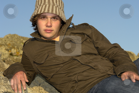 Seat stock photo, Young man at the rocky beach with a hat by Rui Vale de Sousa