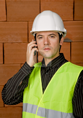 Calling stock photo, Engineer with white hat with a brick wall as background by Rui Vale de Sousa
