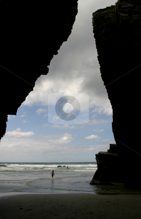 Beach stock photo, Beach cave with some kids in the water by Rui Vale de Sousa