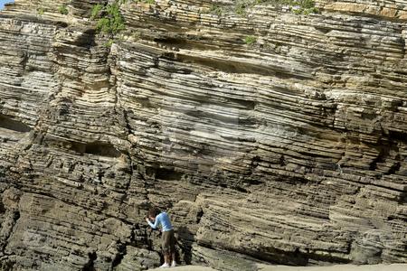 Climbing stock photo, Woman preparing to climb a big rock wall by Rui Vale de Sousa