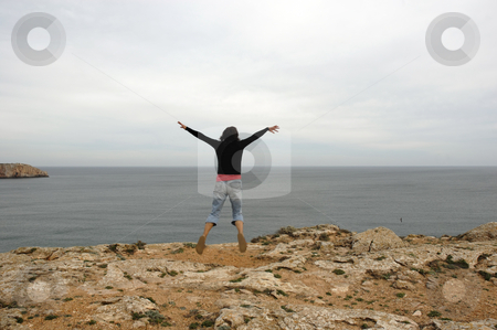 Jump stock photo, Happy woman with arms wide open at the coast by Rui Vale de Sousa