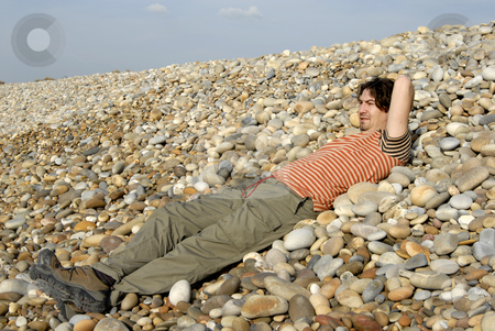 Thoughts stock photo, Young casual man at the beach stones by Rui Vale de Sousa