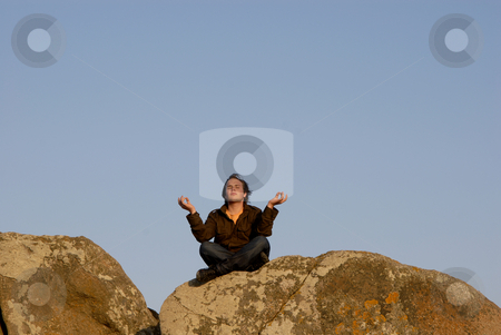 Meditating stock photo, Young man is meditating while sitting on rocks, sunset light by Rui Vale de Sousa