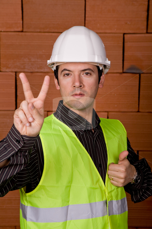 Victory stock photo, Engineer with yellow hat with a brick wall as background by Rui Vale de Sousa