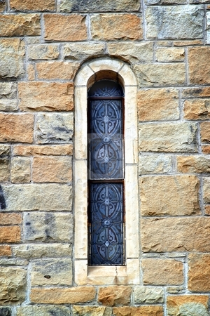Church Window stock photo, Narrow stained glass church window in a rock wall by Henrik Lehnerer