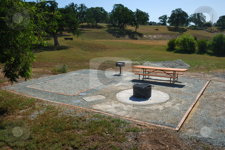 Camping Site stock photo, Camping site with a picnic table, barbecue and fireplace on a sunny day. by Denis Radovanovic