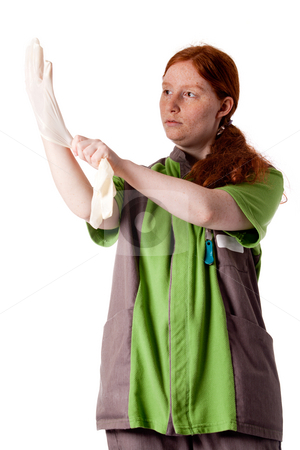 Red haired health care taker putting on her gloves stock photo, Studio shot of health caretaker putting on her gloves. by Frenk and Danielle Kaufmann