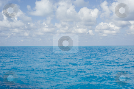 Bahama Surface Clouds Landscape stock photo, Landscape oriented background image of blue ocean water with a partly cloudy sky by A Cotton Photo