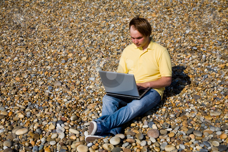 Working stock photo, Young casual man with laptop at the beach by Rui Vale de Sousa