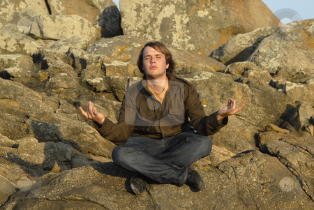 Yoga stock photo, Young man is meditating while sitting on rocks, sunset light by Rui Vale de Sousa