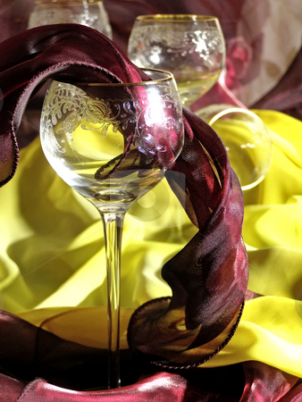 Fabric wine stock photo, Wineglasses against the red and yellow tissue by Sergej Razvodovskij