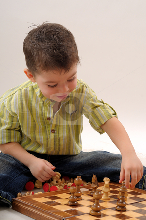Little boy playing stock photo, Little boy playing chess by Dragos Iliescu