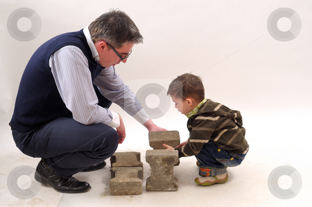 Father and son stock photo, Father and son building with bricks by Dragos Iliescu