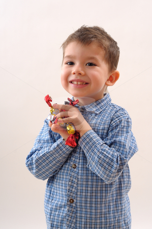 Boy with sweets stock photo, Little boy showing his candies by Dragos Iliescu