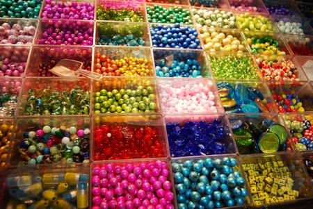 Multicoloured beads in bijouterie shop stock photo, Multicoloured beads sorted in boxes for sale by Leyla Akhundova