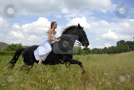 Riding wedding woman stock photo, Galloping beautiful wedding woman on her black stallion by Bonzami Emmanuelle