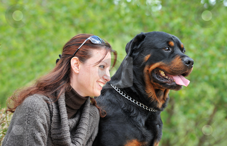 Young woman and her dog stock photo, Beautiful smiling young woman and her purebred rottweiler by Bonzami Emmanuelle