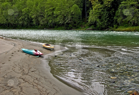 Two Kayaks Along River Bed stock photo, This peaceful photo is of two kayaks laying on a sandy river bed with the gorgeous river and mountains in the scene. by Valerie Garner