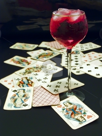 Wine and cards stock photo, Full of red wine and ice wineglass on the table with heap of plaing cards by Sergej Razvodovskij