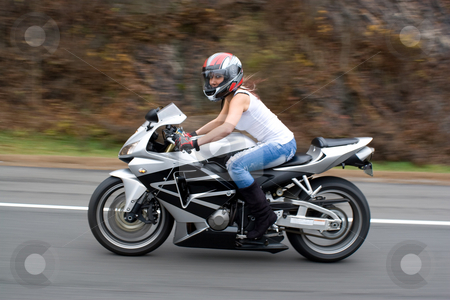 Blonde Biker Girl stock photo, A pretty blonde girl in action driving a motorcycle at highway speeds. by Todd Arena