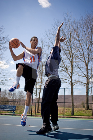 Men Playing Basketball stock photo, Two young basketball players compete fiercely against each other. by Todd Arena