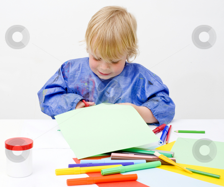 Cutting paper stock photo, Young boy happily cutting his way into a sheet of paper on a table filled with colorful pencils, glue en felt pens by Corepics VOF