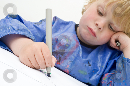 Drawing boy stock photo, Sad looking child making a drawing with a felt-pen. Focus on the felt tip pan and hand by Corepics VOF