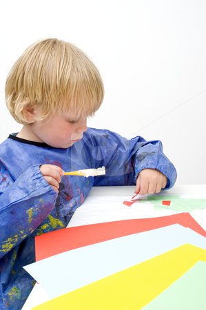 Pasing stock photo, Child pasing pieces of colored paper, using a brush with glue by Corepics VOF