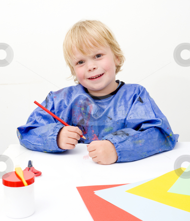 Coloring stock photo, Small child coloring on a large sheet of paper and smiling at the camera by Corepics VOF