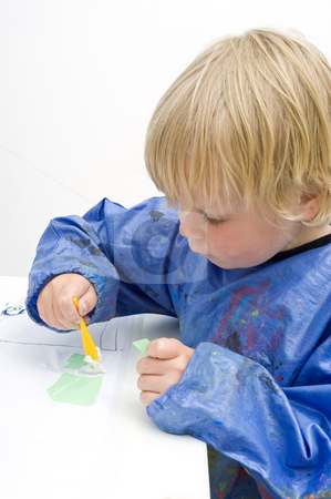 Pasting paper stock photo, Young boy pasing pieces of paper on a table by Corepics VOF